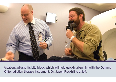 A patient adjusts his bite block, which will help quickly align him with the Gamma Knife radiation therapy instrument. Dr. Jason Rockhill is at left.